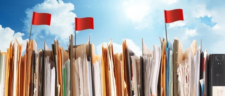 stacked folders with red flags